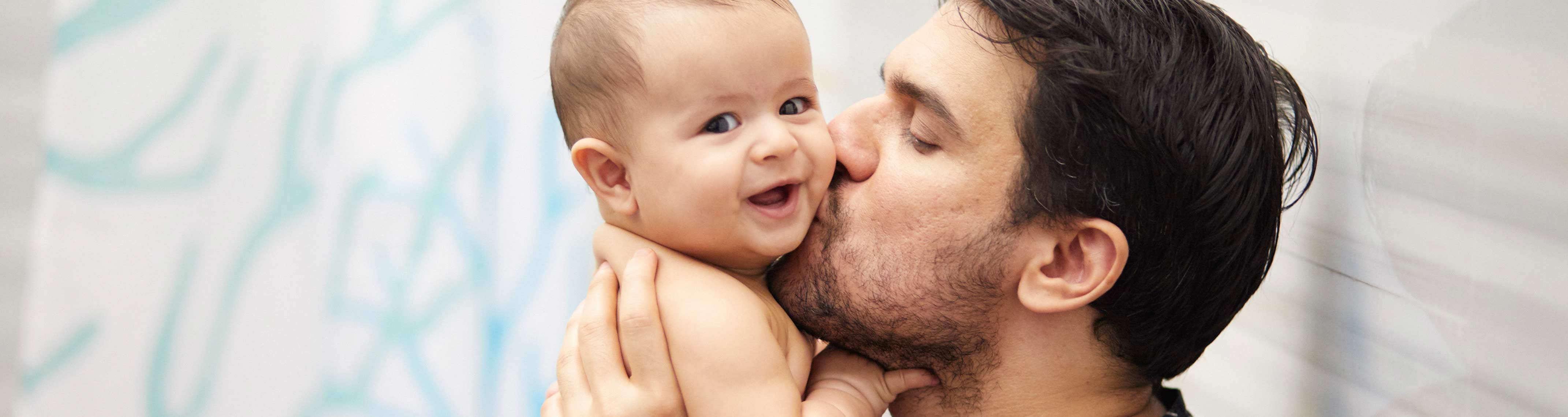 Homem sentado beijando as bochechas de um bebê