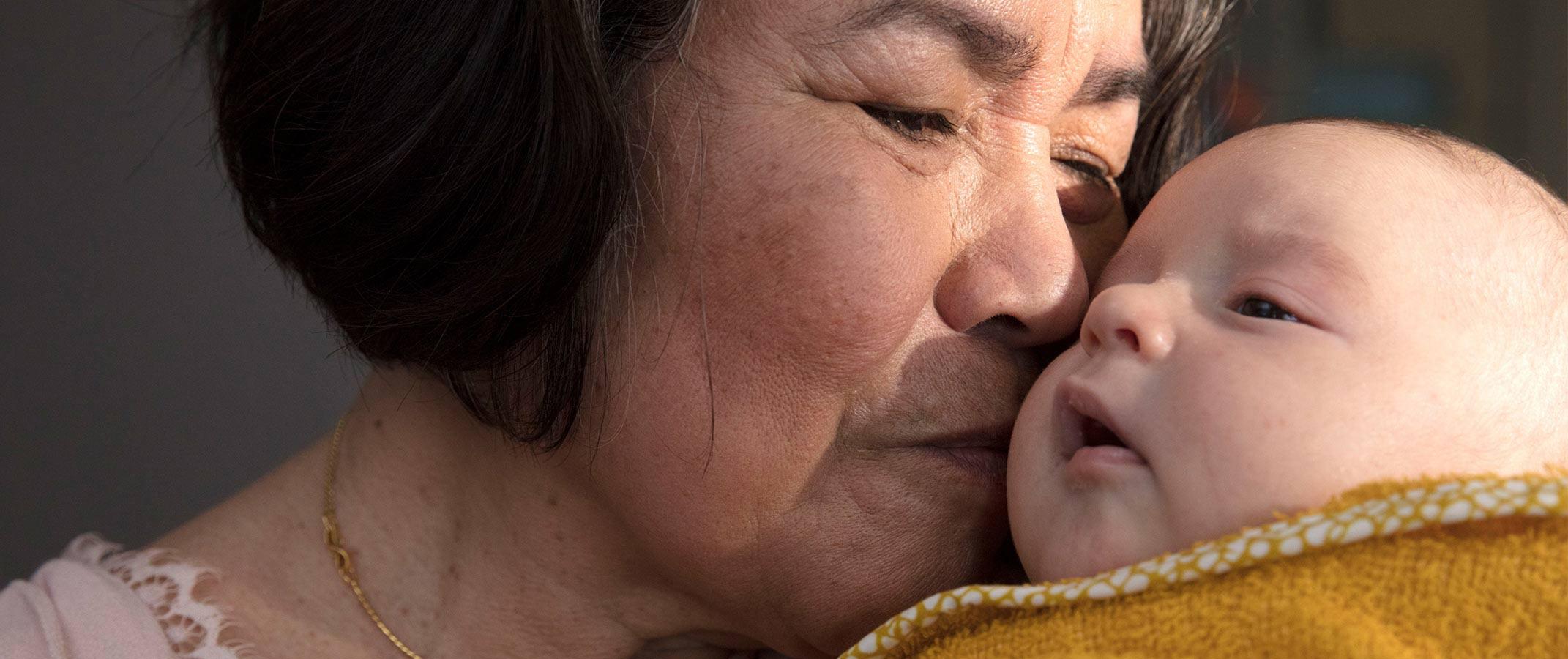 Senhora beijando recém-nascido no colo
