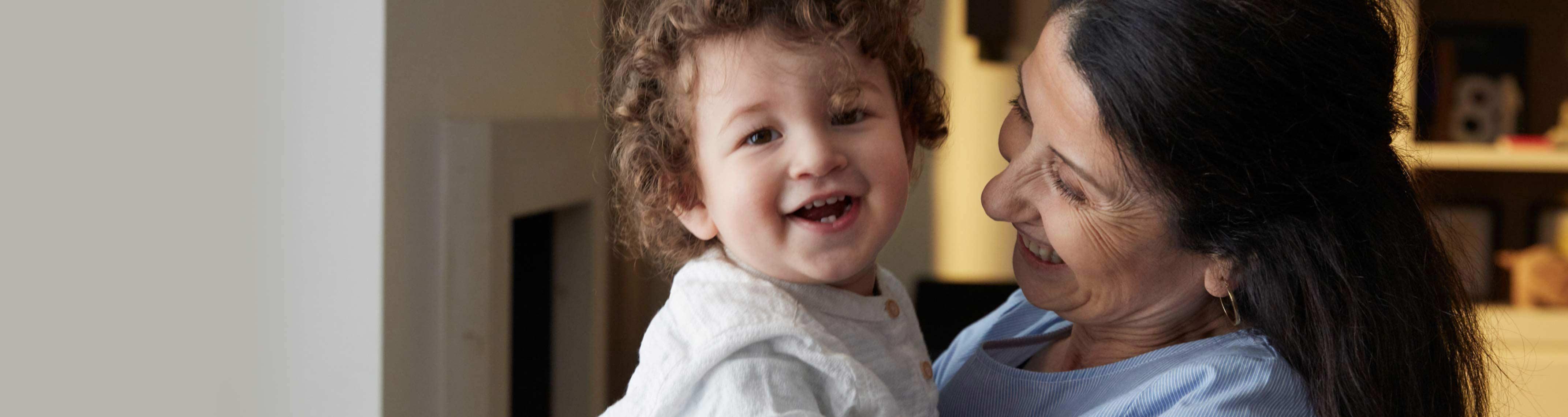 Mulher sorrindo com criança no colo