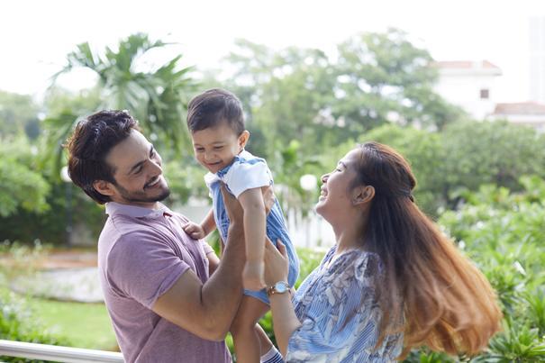 Casal sorridente com bebê num local cercado por natureza