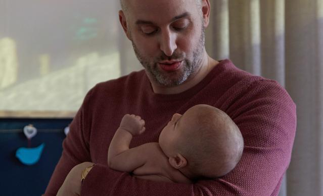 Homem colocando o recém-nascido para dormir
