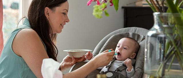 Mulher com um prato na mão alimetando um bebê no carrinho de bebê