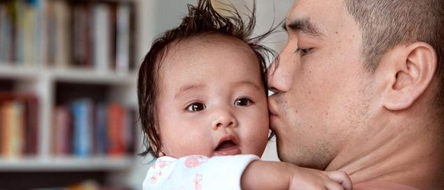 Pai segurando a criança no colo e beijando sua bochecha