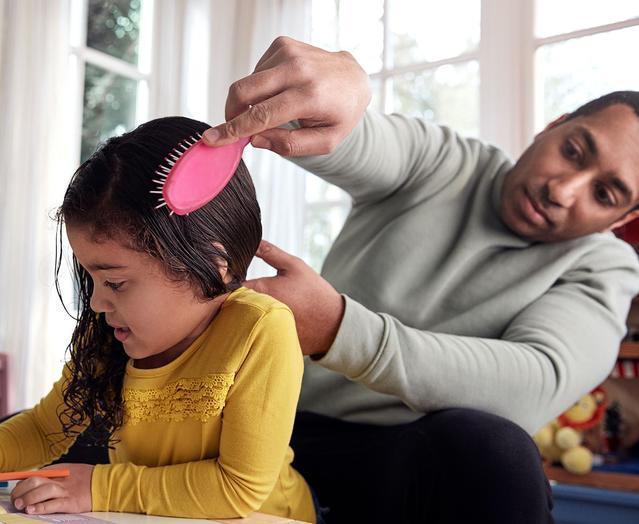 Pai penteando o cabelo da filha