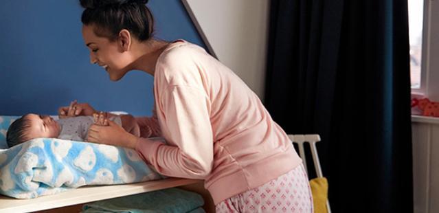 Mulher cuidando de um bebê deitado em cima de um pequeno colchão