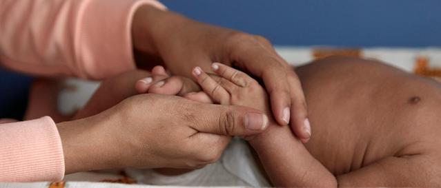 Mulher massageando as mãos do bebê