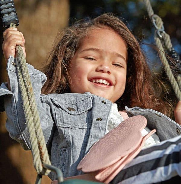 Criança sorrindo num balanço