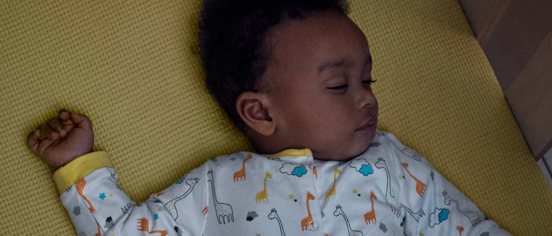 Bebê de pijamas dormindo num berço