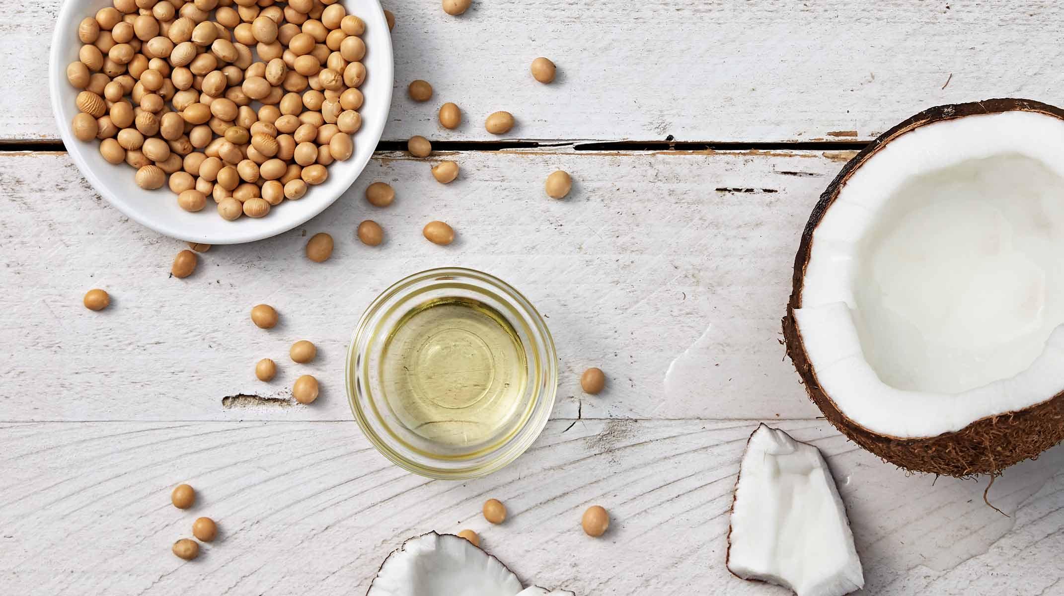 Metade de um coco na mesa, juntamente de óleo e soja num recipiente
