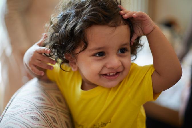 Criança pequena com as mãos na cabeça