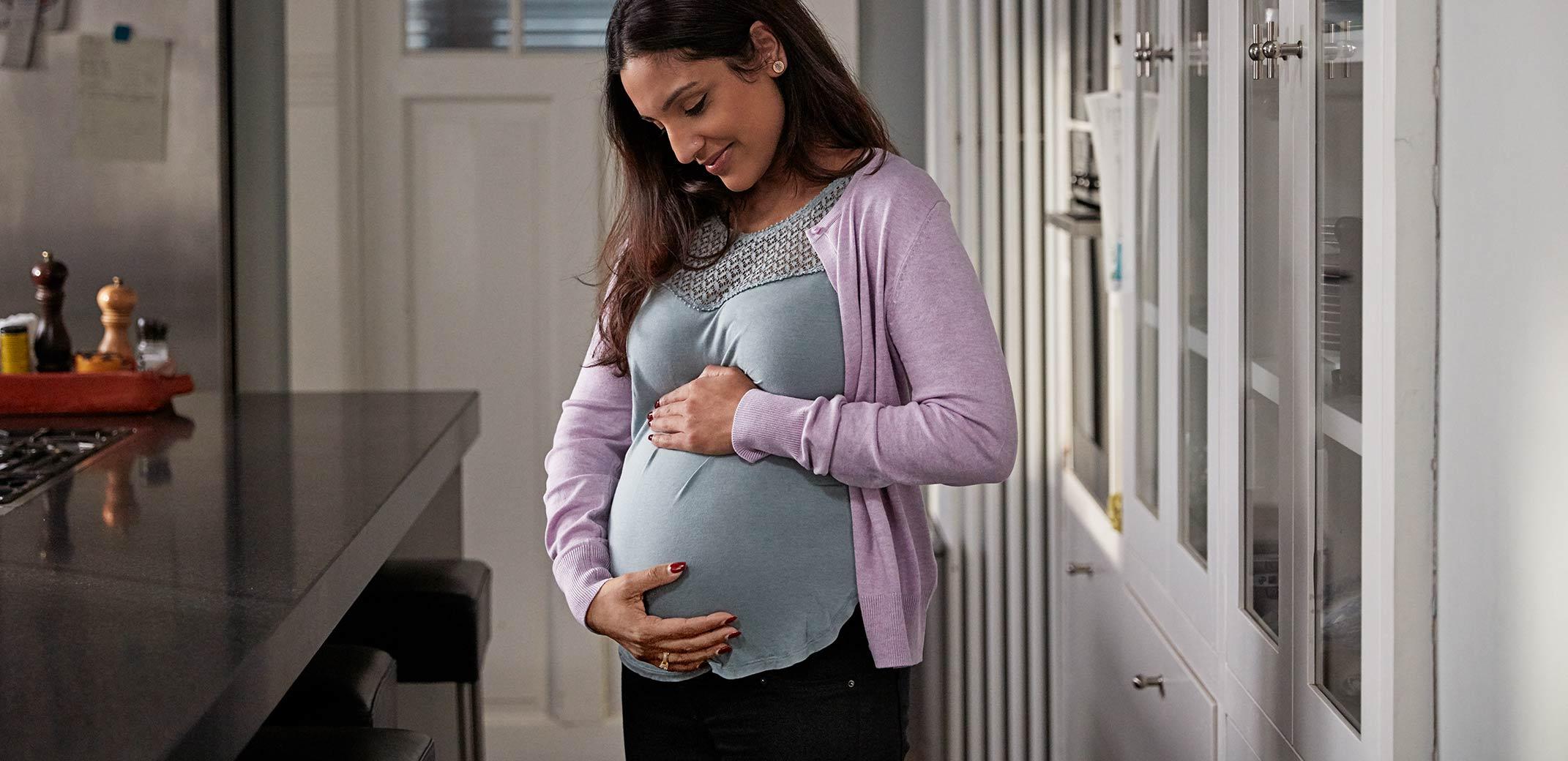 Mulher grávida com mãos na barriga